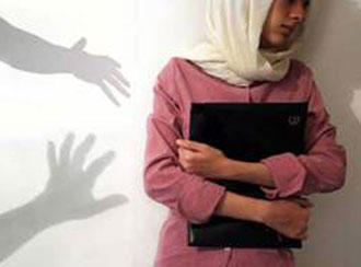 A woman, who is not Sibel, stands with her back to a white wall. Silhouetted against the wall are the shadows of two hands, reaching menacingly towards her.
