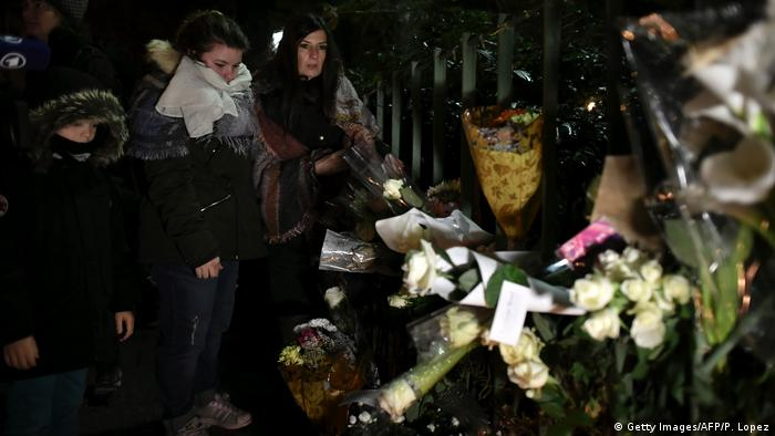 People gather around flowers and candles laid next to the Bataclan concert hall (Getty Images/AFP/P. Lopez)