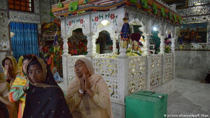 File photo: People pray around the grave of Muslims saint Shah Noorani.