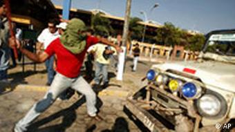 A demonstrator hits a vehicle used by opposition members after they tried to storm a bus station where supporters of Bolivia's President Evo Morales were hiding in Santa Cruz, Bolivia,Wednesday, Sept. 10, 2008. Protesters stormed public offices and blocked roads as a dispute between Morales and Bolivia's energy-rich provinces over tax revenues and a new constitution intensifies.(AP Photo/Dado Galdieri)(AP Photo/Dado Galdieri)