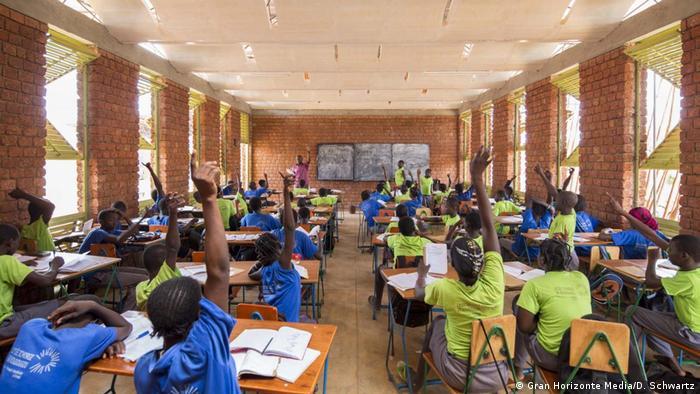 Children raise their hands in a school classroom