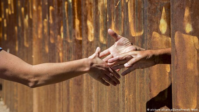 Люди протягивают друг другу руки между стальными балками заграждения на границе между США и Мексикой.