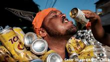 A reveller of Bloco da Latinha, a street carnival group, has some beer during a parade on the last day of carnival in Madre de Deus, Bahia State, Brazil on February 9, 2016. Bloco da Latinha members, mostly fishermen, wear costumes made of aluminium cans, which they start to collect two months before carnival. Each costume weighs about 11-15 kg. After the carnival, all cans are donated to a hospital in Salvador, Bahia. AFP PHOTO / YASUYOSHI CHIBA / AFP / YASUYOSHI CHIBA (Photo credit should read YASUYOSHI CHIBA/AFP/Getty Images)