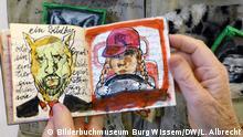 PK Bilderbuchmuseum Burg Wissem in Troisdorf. Die Stücke sind Teil der Ausstellung zu Rotkäppchen Burgi Kühnemann vor ihrem Werk Wolfstaschemit einem ihrer gezeichneten Büchlein