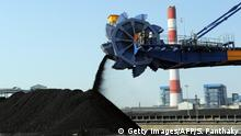 Workers use heavy machinery to sift through coal at the Adani Power company thermal power plant at Mundra some 400 kms from Ahmedabad on February 18, 2011. This is India's first supercritical 660 MW unit. AFP PHOTO / Sam PANTHAKY (Photo credit should read SAM PANTHAKY/AFP/Getty Images)