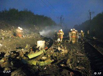 In this photo released by Press Service of Russian Firefighters stand in debris of a Boeing-737-500 scattered around the area of the passenger jet's crash site near rail tracks of the Trans-Siberian railway on the outskirts of the Ural Mountain city of Perm, early Sunday, Sept. 14, 2008, shortly after the crash.