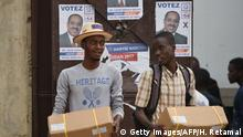 19.11.2016 People carry electoral materials delivered by the Provisional Electoral Council (CEP) one day before of the general elections at a polling station in the center of Port-au-Prince, on November 19, 2016. Twenty-seven candidates will participate in the presidential election to be held on November 20. More than six million Haitians are due to vote in their latest attempt in an 18-month-long effort to choose a president and parliament. / AFP / HECTOR RETAMAL (Photo credit should read HECTOR RETAMAL/AFP/Getty Images)