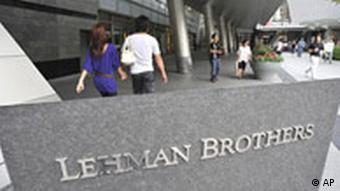 People stroll by a company sign of Lehman Brothers