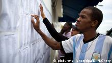 Voters check for their names at a polling station in the Delmas suburb of Port-au-Prince, Haiti, Sunday, Nov. 20, 2016. Haiti's repeatedly derailed presidential election got underway more than a year after an initial vote was annulled. (AP Photo/Dieu Nalio Chery)