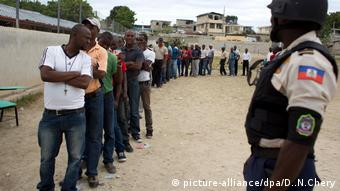 People stand in line to vote during elections in the Delmas suburb of Port-au-Prince