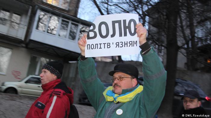 Участник акции протеста с плакатом, на котором написано Свободу политзаключенным