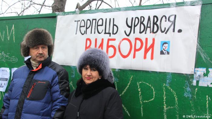 Участники акции протеста на фоне лозунга с требованием проведения выборов