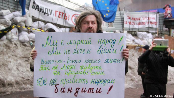 Участник акции протеста с плакатом на Майдане