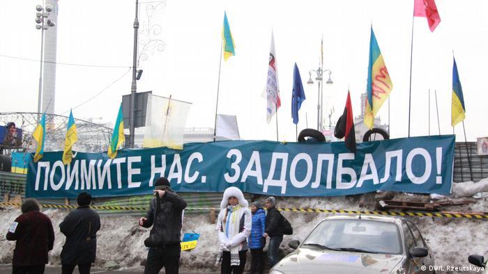 Транспарант с лозунгом, флаги и участники акции протеста