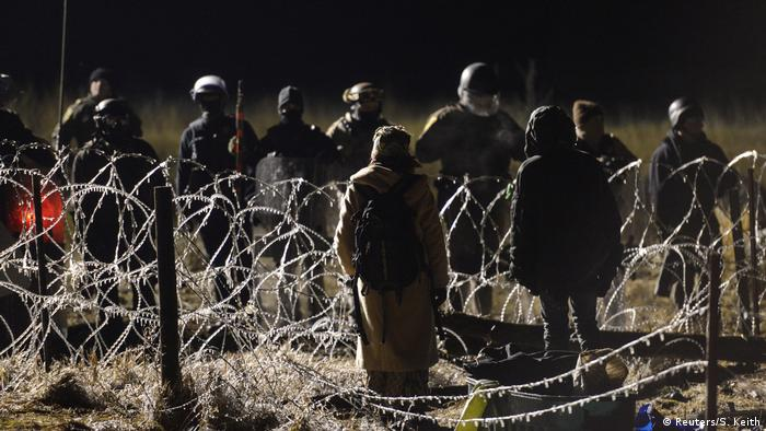 People in a field, barbed wire separates them from police