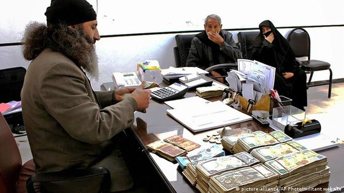 Two Syrian citizens sit in the office of an inheritance judge of the Islamic State militant group in Raqqa, Syria
