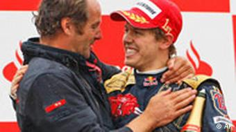 Toro Rosso German driver Sebastian Vettel, right, celebrates on the podium with Toro Rosso team manager Gerhard Berger after winning the Formula One Grand Prix in Monza, Italy, Sunday, Sept.14, 2008.