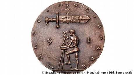 Το χάλκινο μετάλλιο του Βίλφριντ Φιτζενράιτερ αποτυπώνει έναν γλύπτη επί το έργον. Πάνω του η δαμόκλειος σπάθη του ενοικίου για το ατελιέ του. Μια αναφορά στις ένδοξες εποχές για τους κομμουνιστές καλλιτέχνες, που λάμβαναν κρατικό μισθό, αλλά και στις δύσκολες οικονομικά εποχές που ακολούθησαν για τον καλλιτεχνικό κόσμο μετά τη Γερμανική Επανένωση.