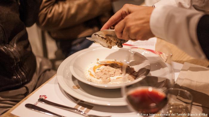 Grating a white truffle (Fiera Internazionale del Tartufo Bianco d'Alba)