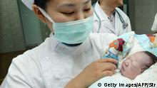 This picture taken on July 17, 2013 shows a nurse holding a new-born baby of Qiu Yan, who was five months pregnant when she was diagnosed with the bird flu virus in April, in a hospital in Zhenjiang, east China's Jiangsu province. A Chinese woman who spent five weeks in intensive care with H7N9 bird flu has given birth to a girl in what was described as a miracle first, according to state media. CHINA OUT AFP PHOTO (Photo credit should read STR/AFP/Getty Images)