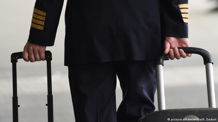 Piloto de avião puxando duas malas