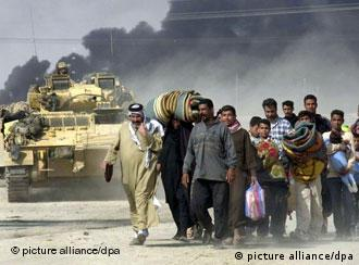 Soldiers watch over Iraqi civilians - a tank and black smoke are in the background