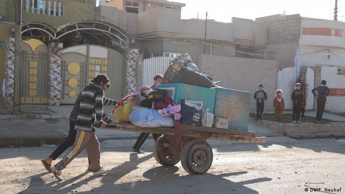 Civilians push their belongings on a cart along a street in eastern Mosul