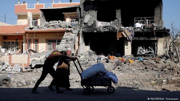 Irak Menschen laufen vor zerstörtes Gebäude (REUTERS/G. Tomasevic)