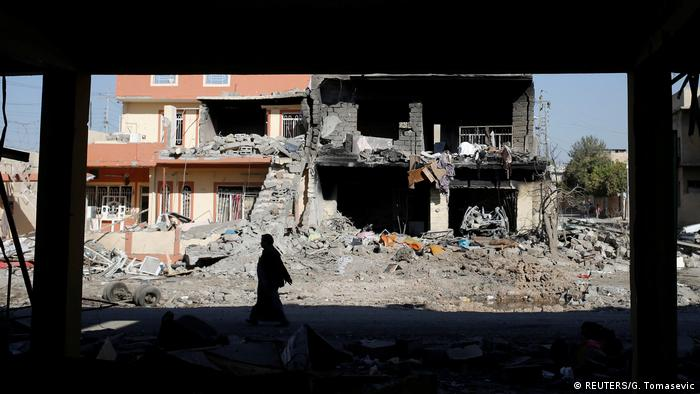 A man walks past a buildign destroyed during clashes between Iraqi forces and 'Islamic State' fighters