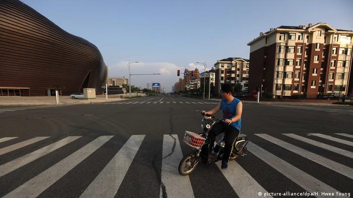 Die Geisterstadt Ordos in China: Teenager mit Fahrrad auf leerer Straße