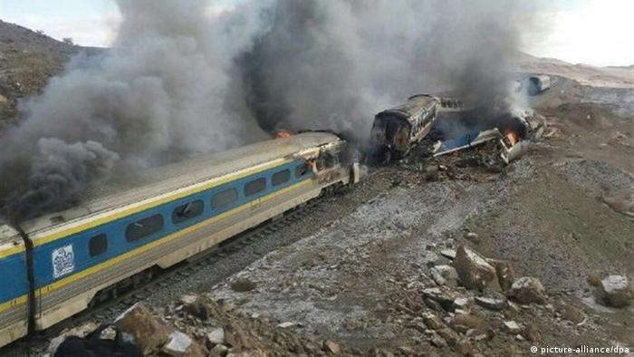 Smoke billows from destroyed train coaches at the site of a train accident in Iran.