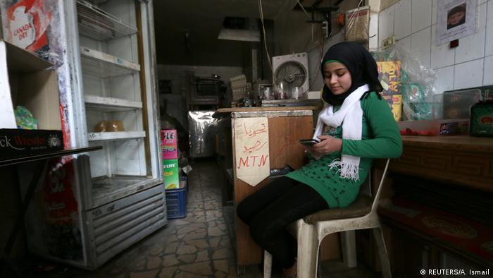 Aleppo Mädchen mit ihrem Mobiltelefon im Lebensmittelgeschäft