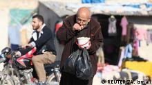 Syrien Mann versorgt sich an Essensausgabe in Aleppo