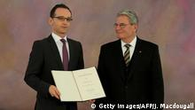 German Justice Minister Heiko Maas (L) poses with his certificate of appointment as German President Joachim Gauck looks on during a ceremony at the presidential palace on December 17, 2013. Angela Merkel was sworn in for a rare third term as German chancellor, capping months of political uncertainty as she bartered with her rivals to help govern Europe's top economy AFP PHOTO / JOHN MACDOUGALL (Photo credit should read JOHN MACDOUGALL/AFP/Getty Images)