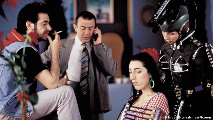 Filmstill Pedro Almodovar Kika 1993 - Szene mit Menschengruppe, zum Teil in Kostümen, telefonierend, rauchend (imago/EntertainmentPictures)