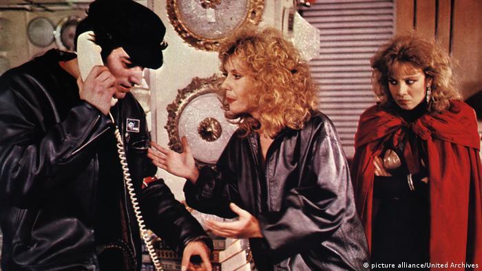 Filmstill Pedro Almodovar Labyrinth der Leidenschaften 1982 - Szene mit Zwei Frauen und einem telefonierenden Mann im Gespräch (picture alliance/United Archives)