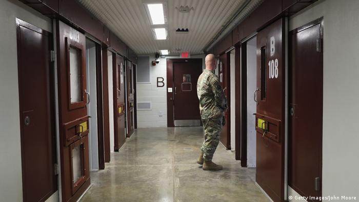 A US soldier looks into a cell at Guantanamo