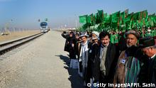 28.11.2016 +++ Officials and Turkmen traditional dancers gather at Turkmenistan's Imamnazar customs point on November 28, 2016 as they watch a freight train heading to Afghanistan's Akina during a ceremony marking the opening of the first section of a $2 billion railway link between the two countries. Asian neighbours Turkmenistan and Afghanistan on November 28 opened the first section of a $2 billion link connecting their two countries by rail for the first time and set to extend to Tajikistan. / AFP / Igor SASIN (Photo credit should read IGOR SASIN/AFP/Getty Images)