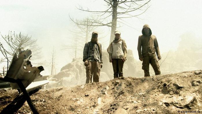 In einer Szene des Films Hell stehen drei Menschen in einer kargen Landschaft