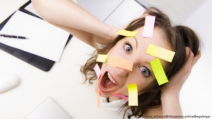 Überforderte Büroangestellte mit vielen Post-Its im Gesicht (picture alliance/Bildagentur-online/Begsteiger)