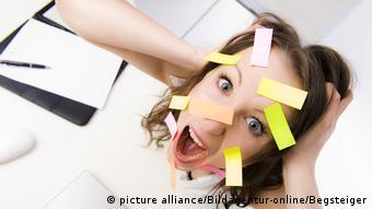 Überforderte Büroangestellte mit vielen Post-Its im Gesicht