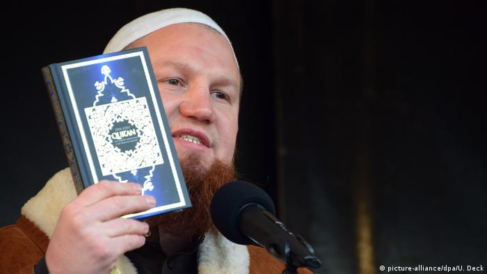 Extremist islamist scholar Pierre Vogel holding up a copy of the Quran