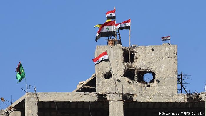Сирийские флаги на разрушенном здании в Алеппо