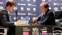 Magnus Carlsen (L), of Norway, takes notes during his match with Sergey Karjakin of Russia in round 12 of the 2016 World Chess Championship match in New York U.S., November 28, 2016. REUTERS/Shannon Stapleton