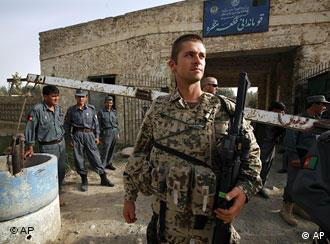 A German ISAF soldier, center, secures a police station with Afghan National policemen