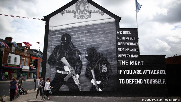 People walk past a mural depicting Ulster Volunteer Force gunmen in mainly Protestant East Belfast, Northern Ireland, in 2011