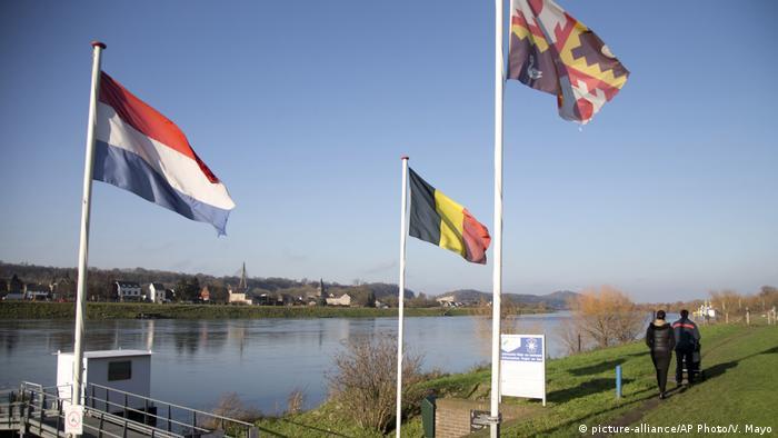 People walk past Dutch and Belgian flags on the waterfront in Eijsden, Netherlands