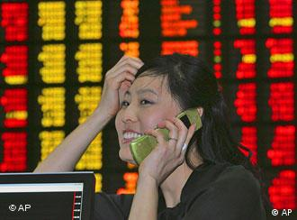 An employee at the Korea Stock Exchange Market smiles in front of an electronic stock board in Seoul, South Korea