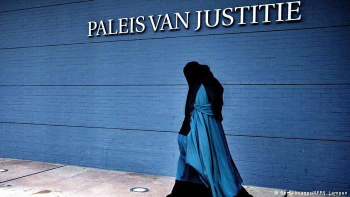A woman wearing a burqa walks past the Palace of Justice in The Hague in 2014
