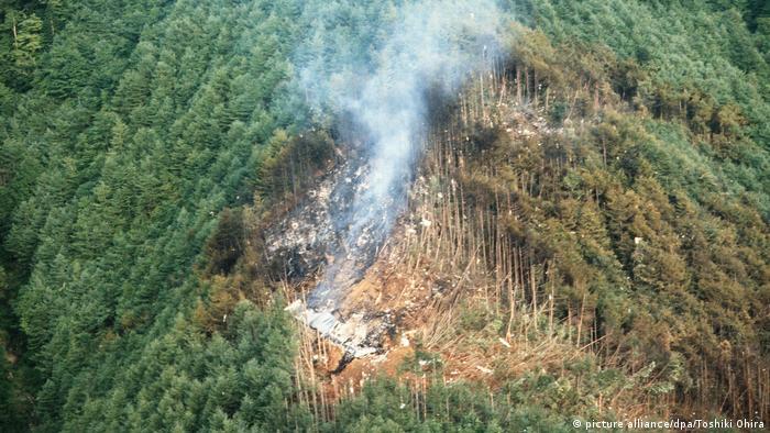Foto aérea de uma clareira aberta em meio à mata, com fumaça saindo dos destroços do avião